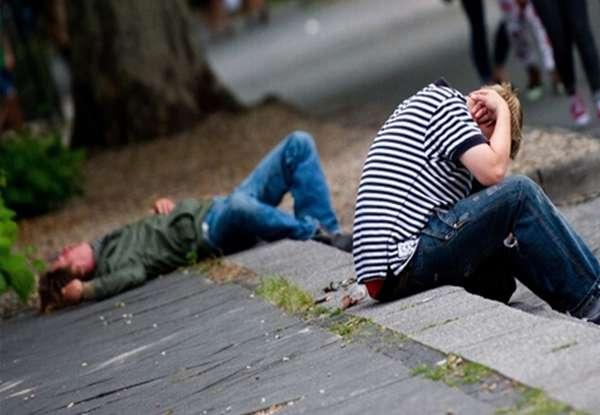 Парень лежит на тротуаре